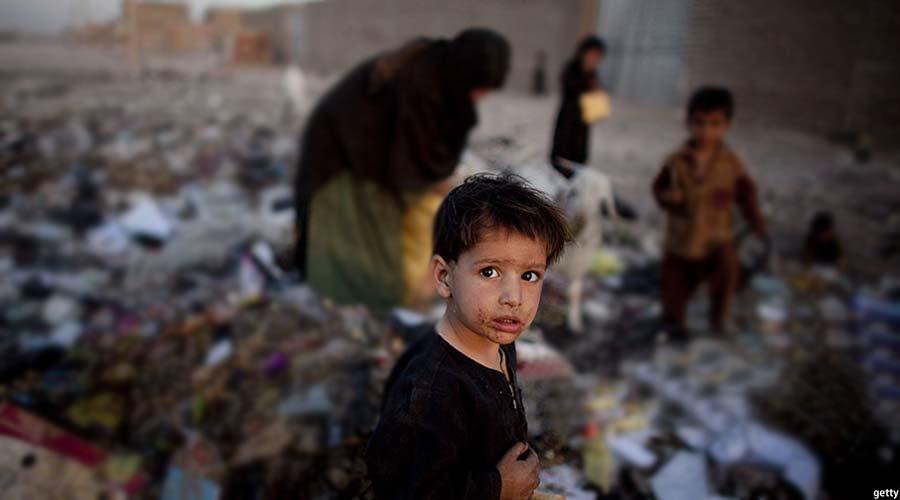 بانوی افغان و کودکاناش در حال جستجو در میان زباله ها