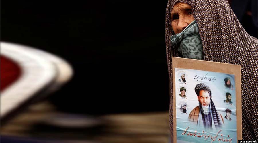 یکی از شرکت کنندگان کهنسال که تصویری از شهید مزاری را در دست دارد