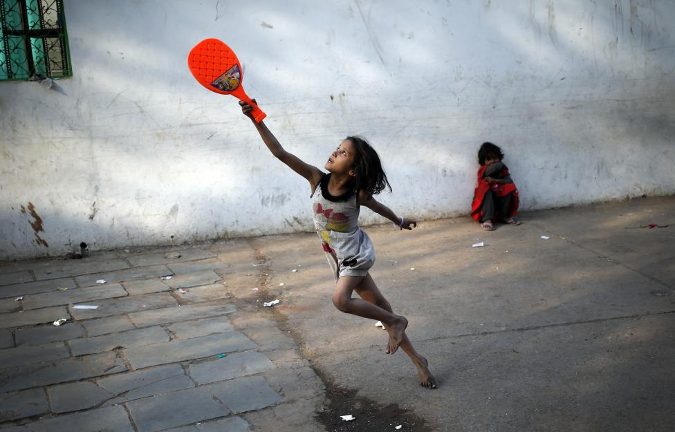 A child plays with a plastic badminton racket in the old quarters of Delhi, March 3, 2016. REUTERS/Anindito Mukherjee
