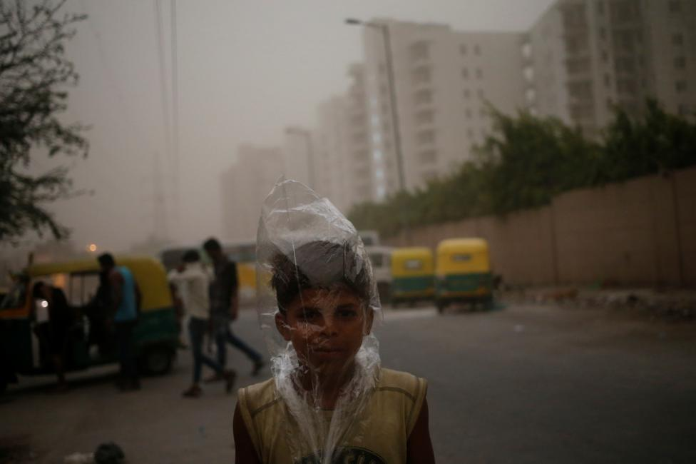 A young boy uses a plastic bag to protect himself from a dust storm in New Delhi, May 23, 2016. REUTERS/Anindito Mukherjee