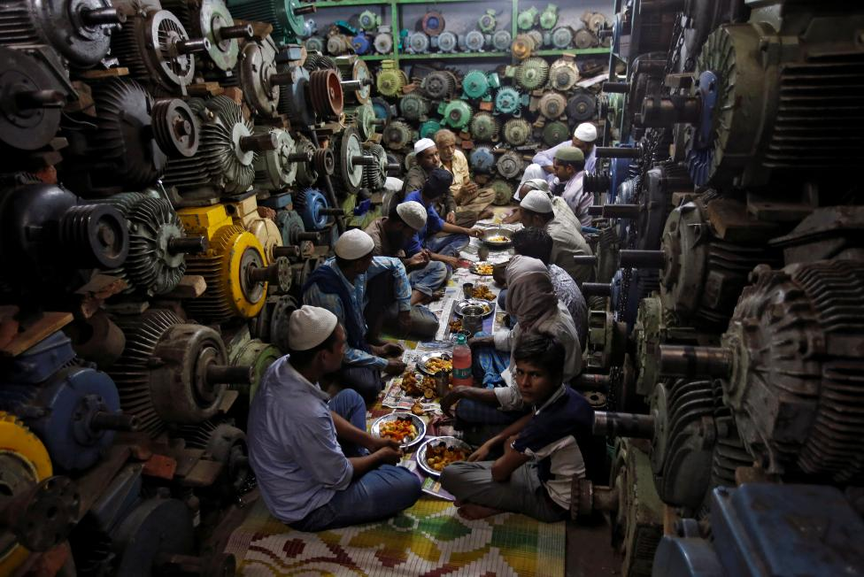 Muslims eat their iftar (breaking of fast) meal at a water pump workshop in the old quarters of Delhi, June 8, 2016. REUTERS/Adnan Abidi