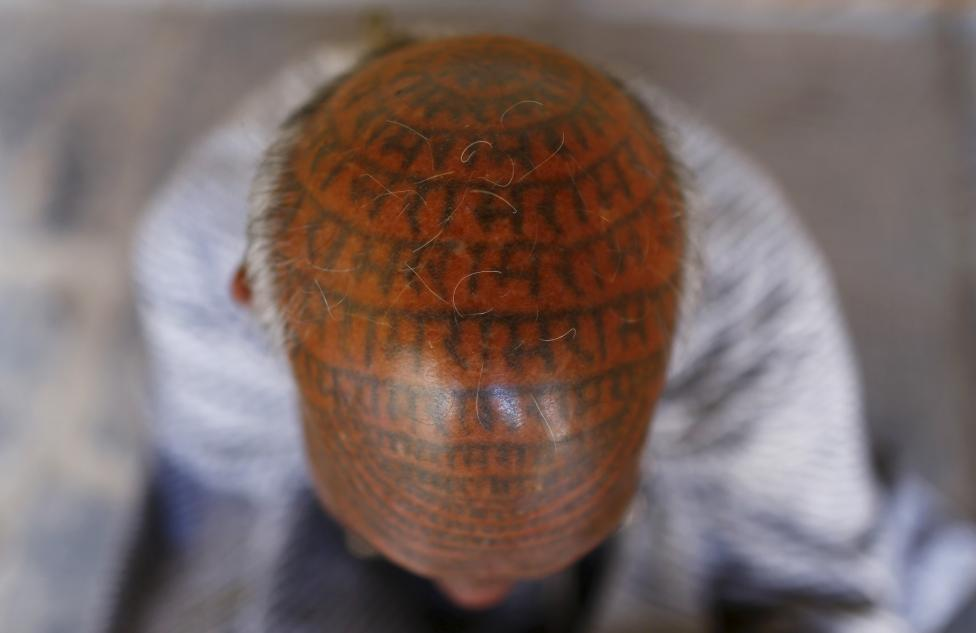 Chanda Ram, 72, a follower of Ramnami Samaj, who has tattooed the name of the Hindu god Ram on his entire face and head, poses for a picture inside his house in the village of Chapora, in the eastern state of Chhattisgarh, November 15, 2015. REUTERS/Adnan Abidi