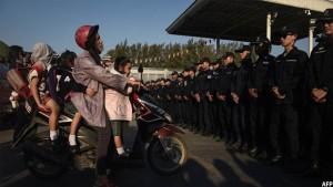 زن تایلندی که می خواهد کودکان اش را به مدرسه ببرد توسط گروهی از پولیس این کشور در نزدیکی معبد وات داماکایا متوقف شده است. تصویر از AFP / عکاس لیلیان سووانرومفا