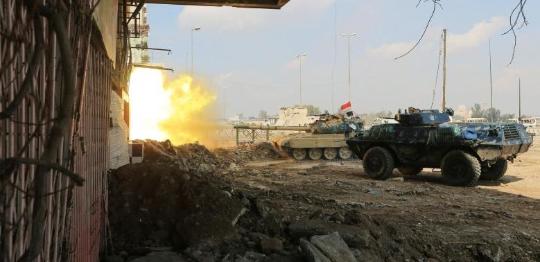A tank of Iraqi rapid response forces fires against Islamic State militants at the Bab al-Tob area in Mosul