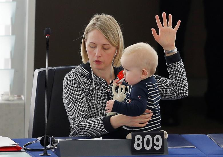 Swedish Member European Parliament Jytte Guteland holds her baby as she takes part in a voting session at the European Parliament in Strasbourg, France. REUTERS/Vincent Kessler