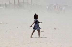 نمایی از طوفان گرد و خاک و دختر خردسال در نزدیکی دریای گنگا در الله آباد هند. تصویر از رویترز