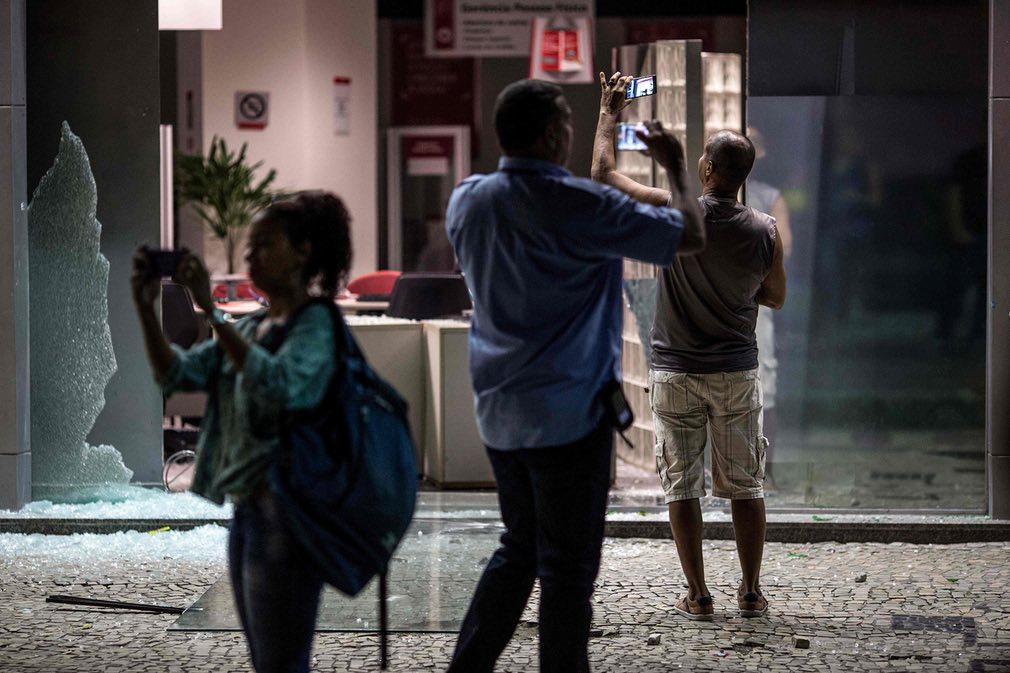 مردم در حال گرفتن عکس از در ورودی یک بانک تخریب شده توسط معترضان طی یک اعتصاب ملی در برابر لایحه اصلاح رفاه اجتماعی دولت برازیل. تصویر از AFP.