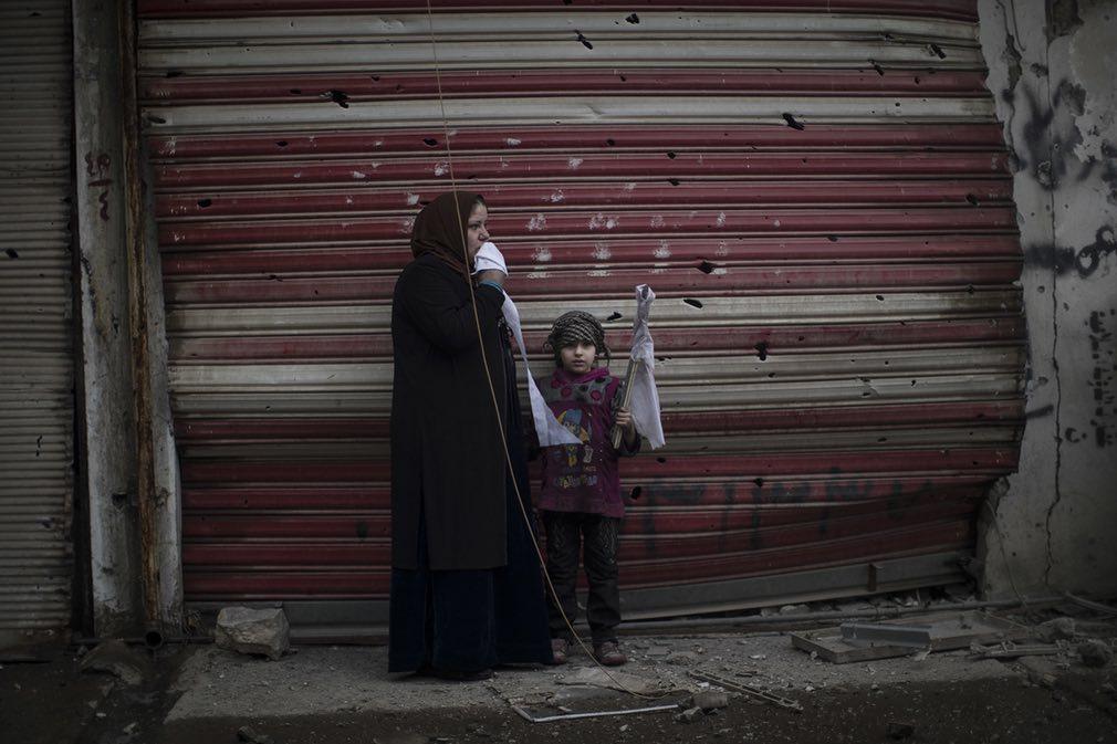 تصویری از دختر خردسال و مادرش که در اثر جنگ میان نیروهای عراقی و گروه داعش خانه شان را ترک کرده و در کنار یکی از جادهها در شهر موصل عراق ایستادهاند. تصویر از AP.