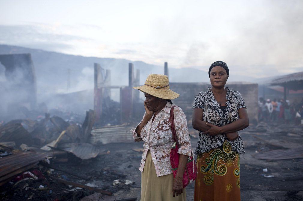 زنان ایستاده در میان بقایای ناشی از آتش سوزی در یکی از مراکز تجاری در شعر پورت آو پرینس. تصویر از AP.