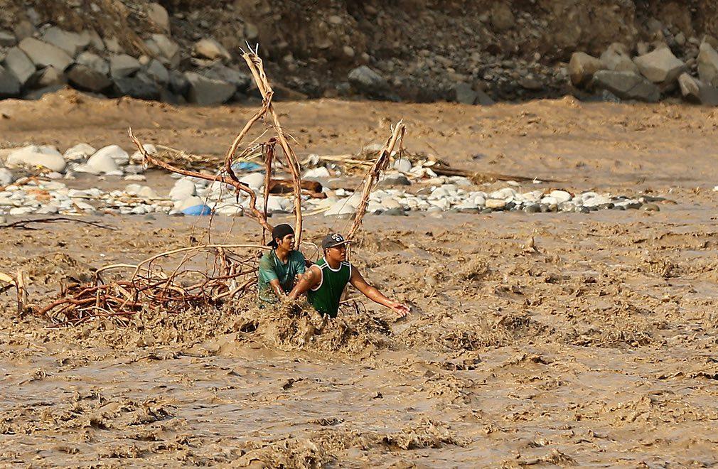 دو پسر جوان در حال عبور کردن دریای ریماک در شهر لیمای پیرو. تصویر از Reuters.