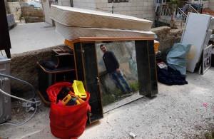 مرد فلسطینی بعد از آنکه خانه شان توسط اسکواترهای اسرائیلی فروریخته شد در کنار وسایل خانه  خود ایستاده است. تصویر از AFP