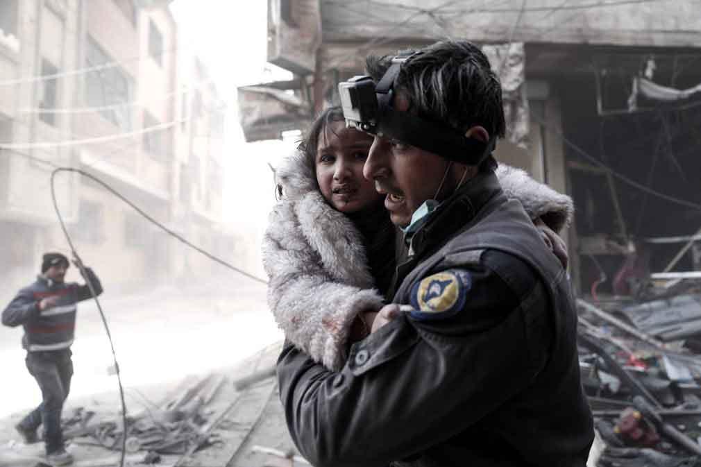 یکی از سربازان نیروهای دفاعی غیر دولتی سوری، دختر خردسالی را که در اثر حمله هویی مجروح شده است به آغوش گرفته. تصویر از Getty