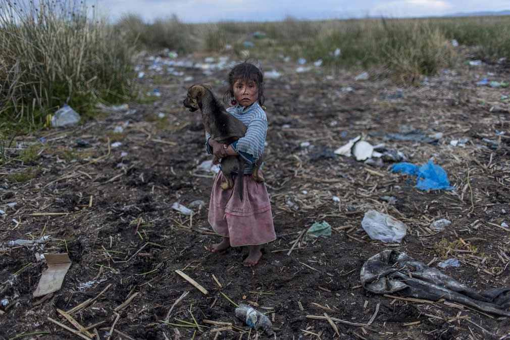 دختر خردسالی ایستاده در میان زبالهها در یکی از روستاهای دور افتاده در پیرو. تصویر از AP