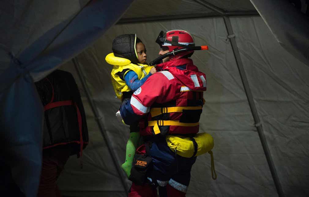 کودک مهاجر آفریقایی که توسط یکی از کارمندان صلیب سرخ در مالاگا، یکی از بندرهای اسپانیای جنوبی نجات داده شده است. تصویر از AFP