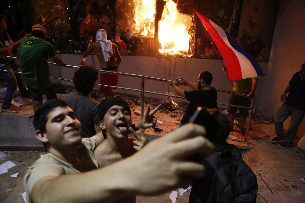 دو جوان حین ژستگرفتن برای عکس سلفی در بیرون ساختمان کنگرهی پاراگوای. این دو درست زمانی که درگیری بین پولیس و معترضانِ مخالف اصلاح قانون پیشنهادی برای انتخاب مجدد رییسجمهوری اوج گرفته بود، با چنین رویکردی ظاهر شدند / عکس: ای پی