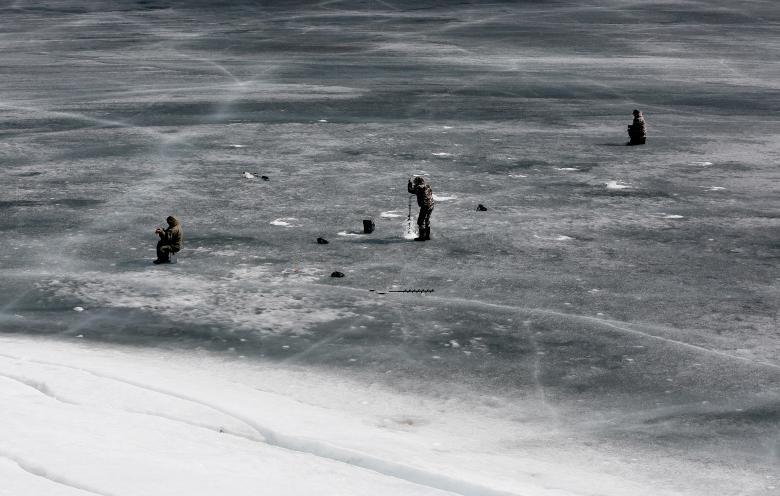 ماهیگیران روس حین ماهیگیری از دریای که تمام آنرا یخ بسته است / عکس: رویترز