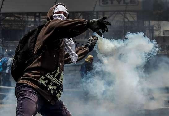 یک مظاهره کننده حین بازپرتاب نارنجک دودزا به سمت سربازان وینزویلایی. این تظاهرات بر علیه دولت نیکولاس مادورو رییس جمهور آن کشور از چندی به این سو راهاندازی شده است. / عکس: آژانس خبری فرانسه