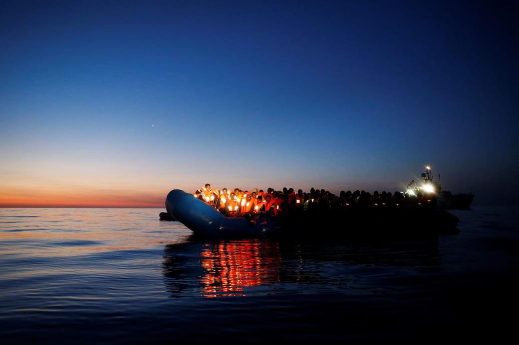 یک قایق پر از مهاجر چراغ بهدست در انتظار ناجی. این تصویر توسط درین زمیت لوپی عکاسخبرنگار رویترز در سپیدهدم از آنان شکار شده است.