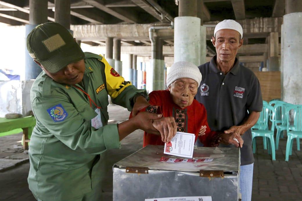 کارکنان یک شعبهی انتخاباتی در جریان کمککردن به یک زن مسن تا رای خود را در صندوق رایدهی بی اندازد / عکس: اسوشیتت پرس
