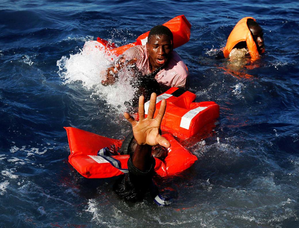 مهاجران در تلاش به دستآوردن جلیقههای نجات؛ این تصویر پس از غرقشدن قایق لاستیکی آنان و عملیات نجات توسط سازمان غیر دولتی مالت در آبهای مدیترانه، گرفته شده است. / عکس: رویترز