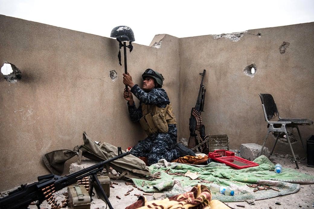 این تصویر توسط کارل کورت زمانی ثبت شده که یک سرباز فدرال عراقی با بلند کردن کلاه یکی از همرزمان خود، در تلاش جلب تیراندازی تکتیرانداز داعشی بوده است. / عکس: گیتی