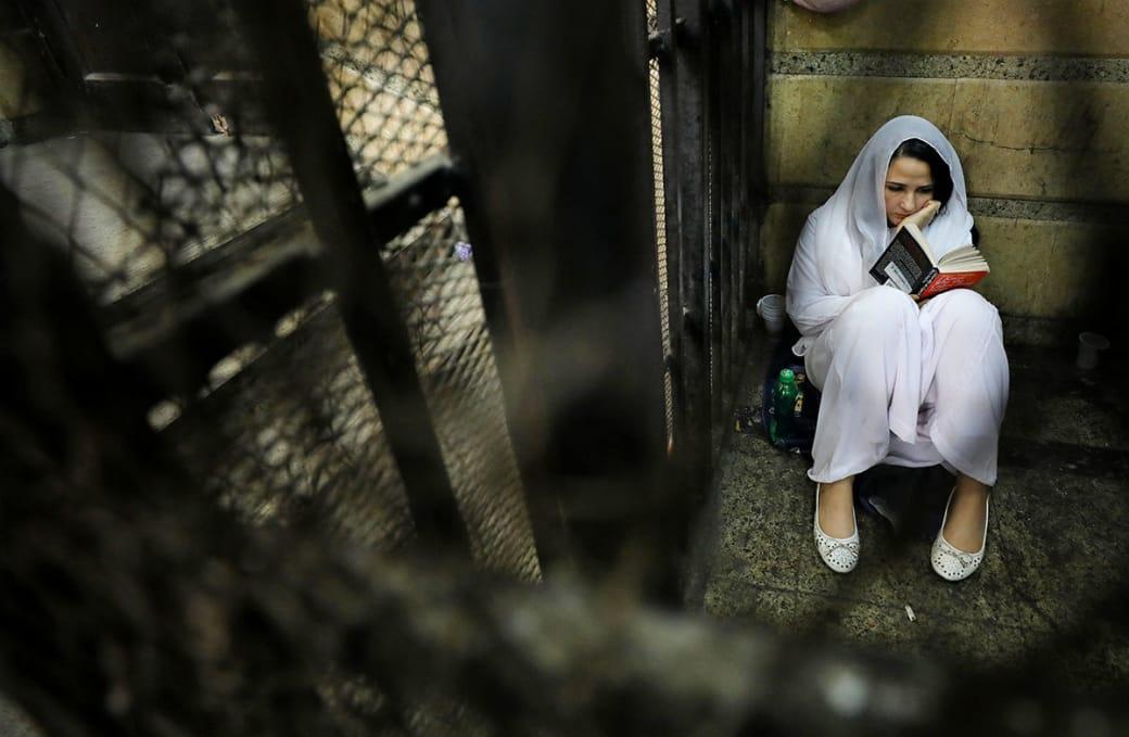 ایا حجازی؛ بنیانگذار «Belady» یک سازمان غیر دولتی به منظور ترویج زندگی بهتر برای کودکان خیابانی، حین خواندن یک کتاب در پشت میلههای زندان در قاهره پایتخت مصر. خانم حجازی در 23 ماه مارچ به اتهام قاچاق انسان دستگیر و زندانی شده بود اما بلاخره در 20 همین ماه برائت گرفت و از زندان آزاد شد. او اکنون در آمریکا پناهنده شده است. / عکس: رویترز