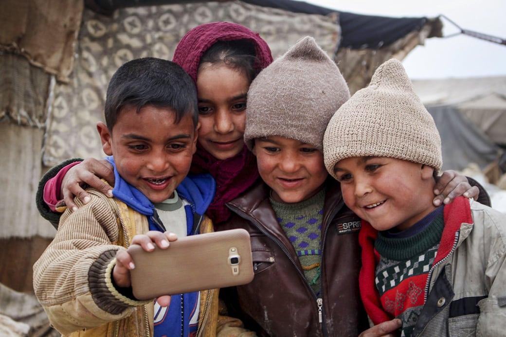 کودکان آوارهی سوری حین گرفتن عکس سلفی در یکی از اردوگاههای موقتی، در خیمهای در غوطهی شرقیِ دمشق. / عکس: گیتی