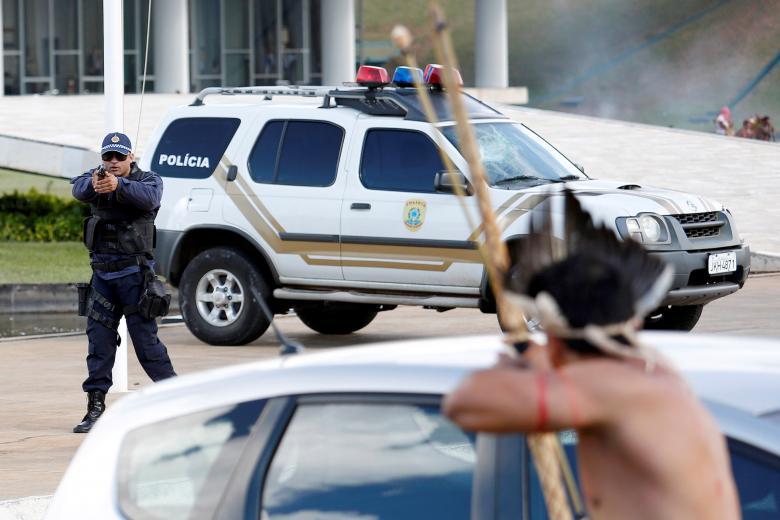 پولیس ضد شورش برازیل در جریان گرفتن اسلحه به سمت یک سرخپوست برازیلی که به علت نقض حقوق مردم بومی آن کشور در برازیلیا پایتخت آنکشور دست به تظاهرات زده بودند. جالب اینجاست که این برزیلی بومی با تیر و کمان خود اما پولیس را نشانه گرفته است. / عکس: رویترز
