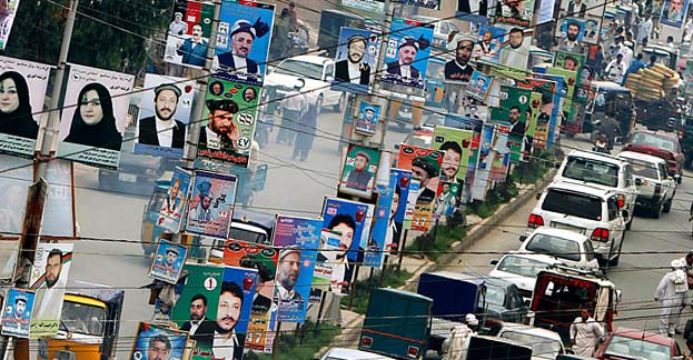 Election posters line a street in Jalalabad, east of Kabul, Afghanistan, on Monday, Aug. 16, 2010. Afghans will go to the polls for parliamentary elections in September. (AP Photo/Rahmat Gul)