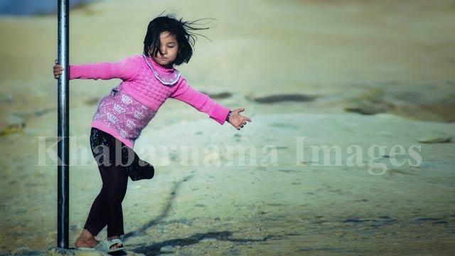 رقص در باد... دختری کوچک در حال تاب خوردن به دور میلهی فلزی/ غرب کابل، دشت برچی، تپه کتهبلندی عکس: ذکی امینی / خبرنامه