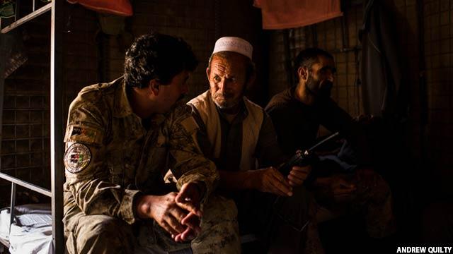 غلام سخی در حال صحبت با یک عضو ارتش ملی افغانستان و جنگجویان پولیس محلی افغان داخل یکی از پایگاه های پولیس محلی