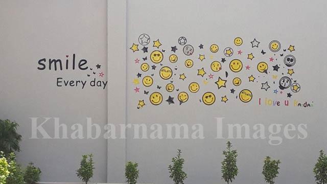 """بر دیوار ساختمان اصلی مکتب جمله همیشه """"لبخند بزن"""" را به حروف انگلیسی نوشته اند که در ادامه آن شکلکهای متفاوتی از ایموجیها با طرح لبخند نقاشی شده است"""