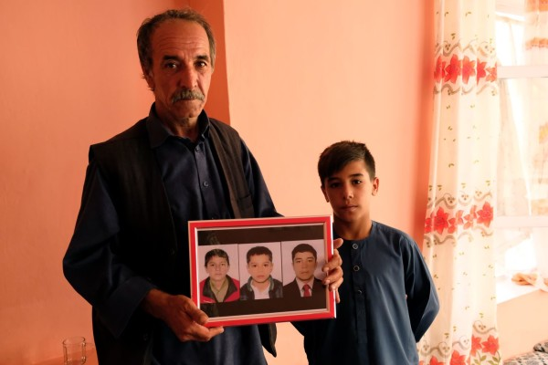 عبدل محمد الیاسی، 55 ساله و احمد سهیل 12 ساله، عکس 3 تن از اقارب شان که در حمله 17 اگست گروه داعش بر تالار عروسی در کابل کشته شدند به دست دارد. از سمت چپ به راست، عبدل نقیب الیاسی، 16 ساله، آرش الیاسی 13 ساله و عبدل قدیر الیاسی، 18 ساله / عکس: واشنگتن پست