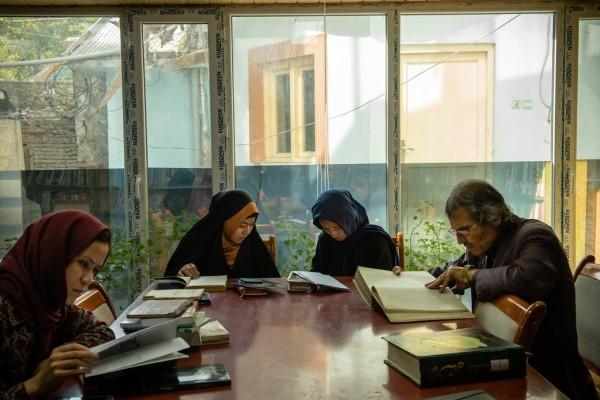 دو دانشجو که موضوع پایان نامه شان در باره زندگی و شعر آقای وجودی است، در منزل اول کتابخانه قبل از ملاقات با او. عکس: نوییورک تایمز