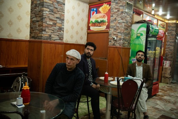 یک خدمه و مشتریان در رستورانتی در کابل به تلوزیون خیره شده بودند تا امضا تفاهمنامه تاریخی روز شنبه را ببینند یا تماشا کنند