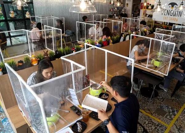 رستورانی را در بانکوک نشان میدهد که مردم با رعایت فاصله غذا میخورند.
