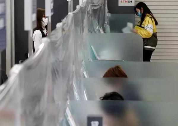 . تصویر بانکی در ژاپن که در مقابل باجههای آن پردهای پلاستیکی نصب شده