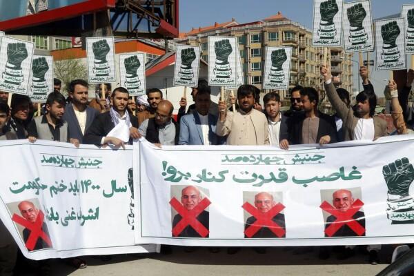 تظاهرکنندگان ماه گذشته هنگام اعتراض به درج قومیت در تذکره در کابل، پوسترهای آقای غنی را  در دست داشتند.. جاوید کارگر