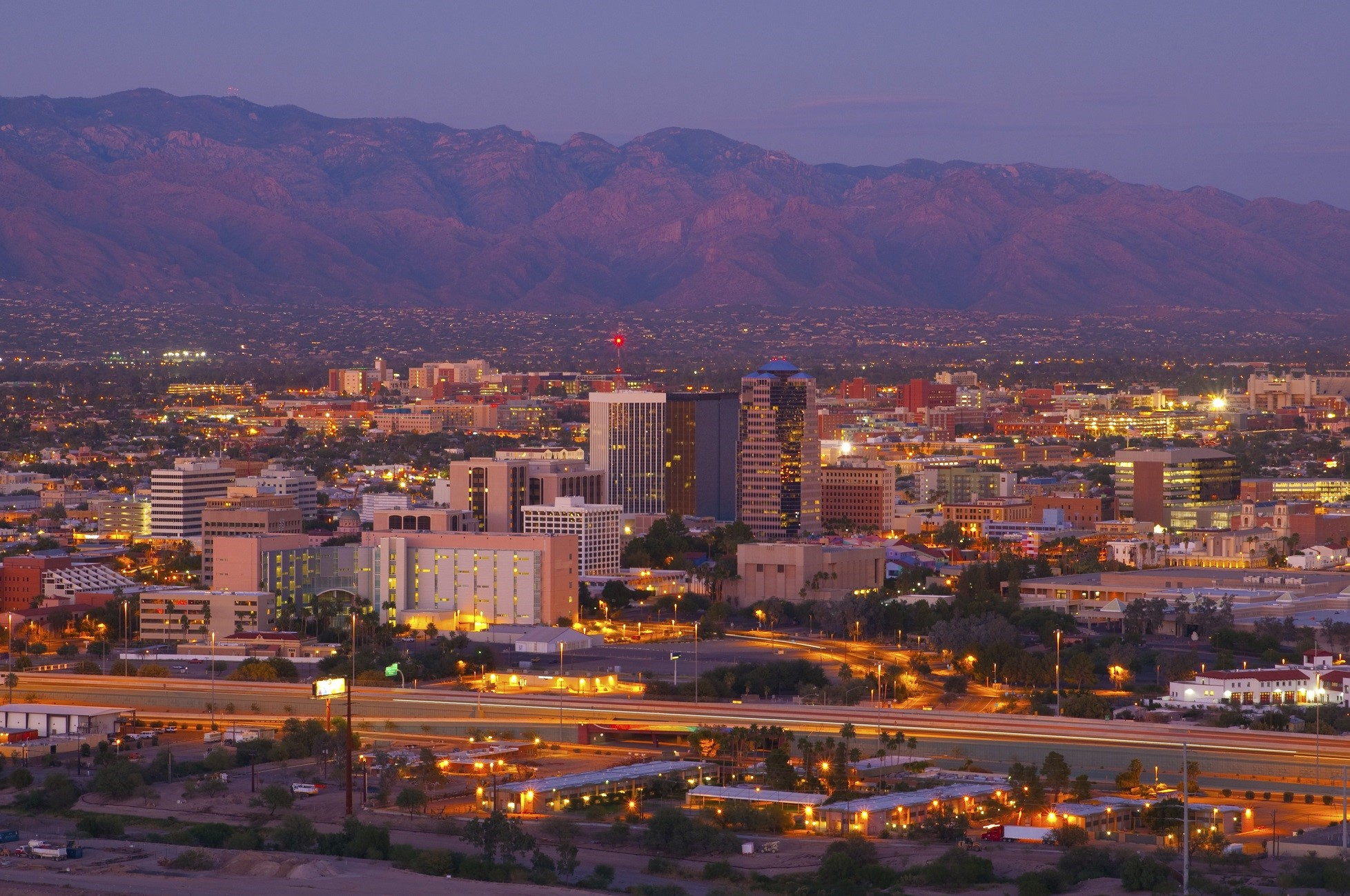 Tucson downtown skyline and aerial overview (including the University of Arizona) w/ Catalina Mountains at dusk.
